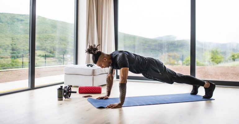 A fit mixed race man with dreadlocks doing exercise at home.